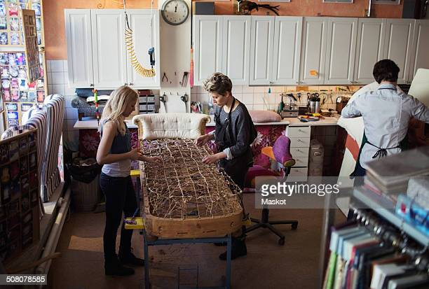 Female workers making chaise longue together at workshop