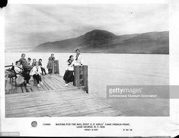 Female workers of General Electric wait for the mail boat at a dock on Lake George They are vacationing at French Point Camp a GEowned facility