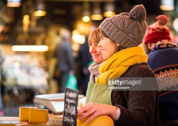 female workers on cheese stall at borough market, london, uk - borough market stock pictures, royalty-free photos & images