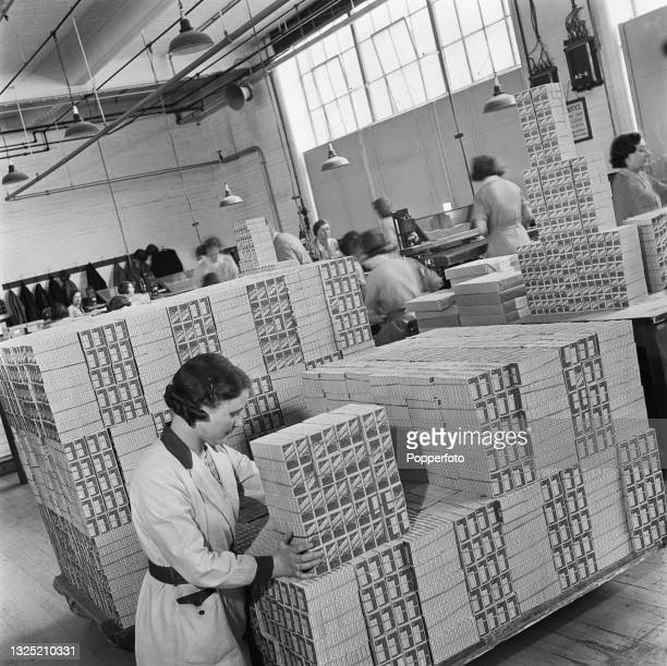 Female workers package up pallets of boxes of cigarette packets ready for distribution at a cigarette factory in England during World War II on 21st...