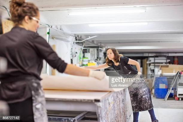 Female workers positioning manufactured object on table