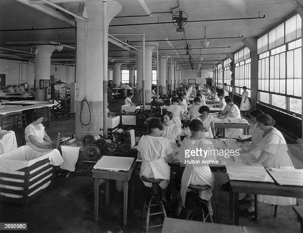 Female workers starch shirt collars and use presses while sitting around tables inside a garment factory. They wear white smocks.