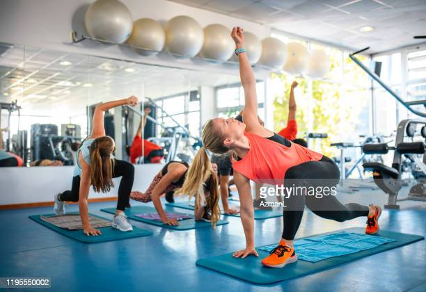 female workout instructor leading group in stretches - sports venue stock pictures, royalty-free photos & images