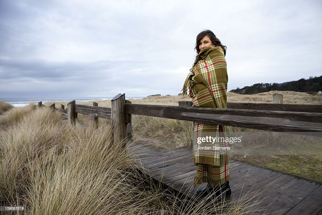 Female wrapped in blanket at beach. : Photo