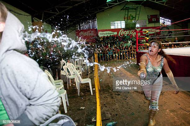 Female wrestler throwing water at audience member splash Lucha Libre wrestling origniated in Mexico but is popular in other latin Amercian countries...