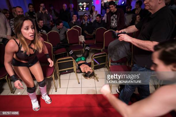 Female wrestlers are pictured during a show on March 11 in Nanterre, near Paris. - In Nanterre, the French Association of Professional Wrestling...