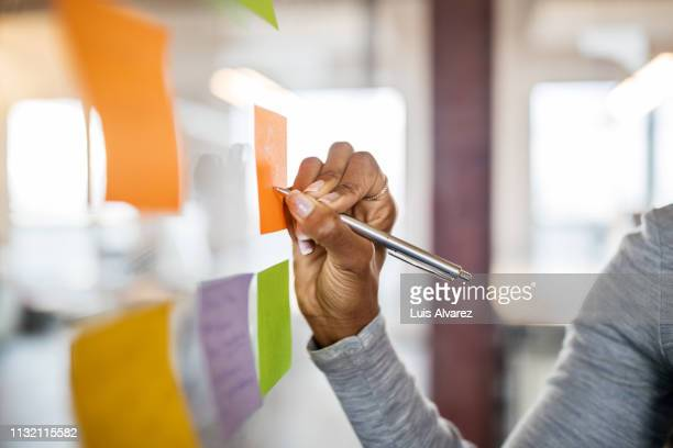 female writing new ideas on sticky note - strategia foto e immagini stock