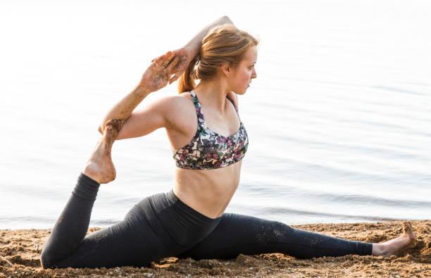 Female yogi in advanced split on the sand