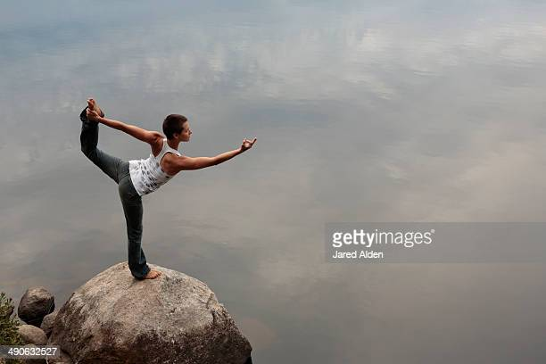 female yogi practicing yoga on a rock by still water - yogi stock photos and pictures