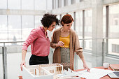 Female young architects with model of a house standing in office, talking.