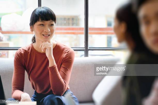 female young asian entrepreneur smiling and discussing ideas with colleague - small group of people stock pictures, royalty-free photos & images