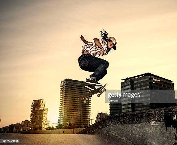 Female young skateboarder jumping in skatepark in the city