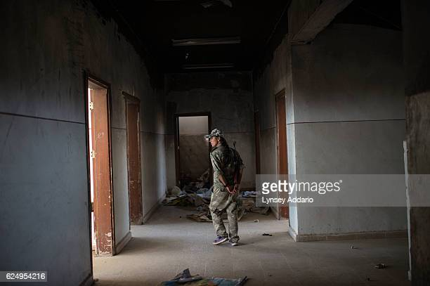 HASAKA SYRIA A female YPG soldier walks through an abandoned school in the former ISIS and Jabat al Nusra stronghold of Tel Bark which was taken over...