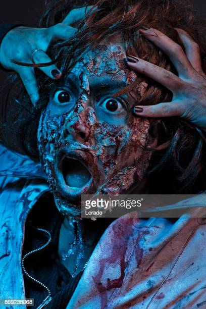 female zombie nurse alone with curly red hair - horror movie stock photos and pictures