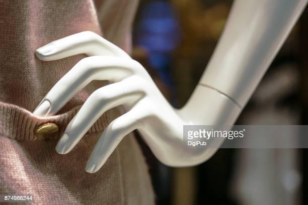Female-like mannequin's right hand on porket