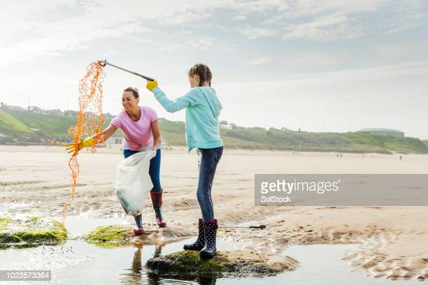 Females Collecting Plastics and Rubbish Off a Beach