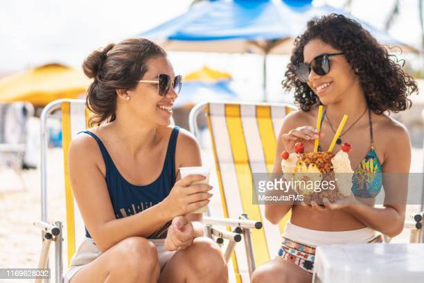 females drinking tropical juice at the beach - porto galinhas stock photos and pictures