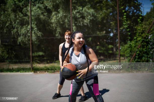 females enjoying playing basketball on court - passing sport imagens e fotografias de stock