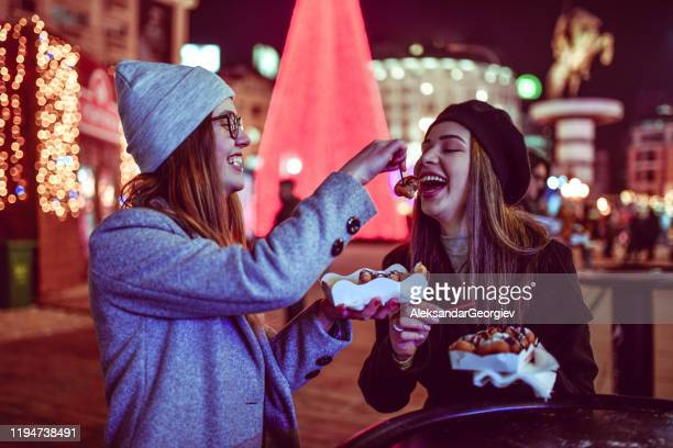 females feeding each other with donuts - downtown comedy duo stock pictures, royalty-free photos & images