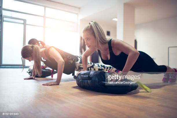 females group doing push-up exercises in plank position at gym - waistcoat stock photos and pictures