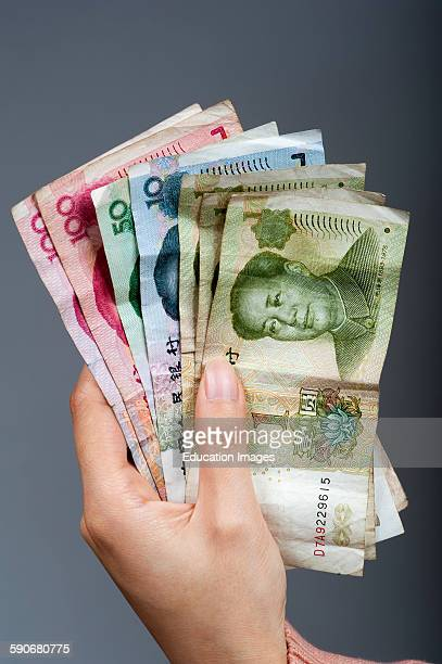 Female's hand holding Chinese banknotes