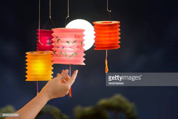 Female's hand holding colourful lanterns on full moon sky background.