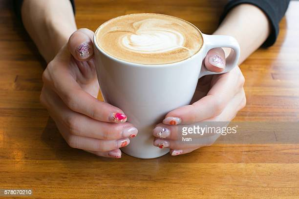 A female's hands with heart nail art is holding a cafe with latte art
