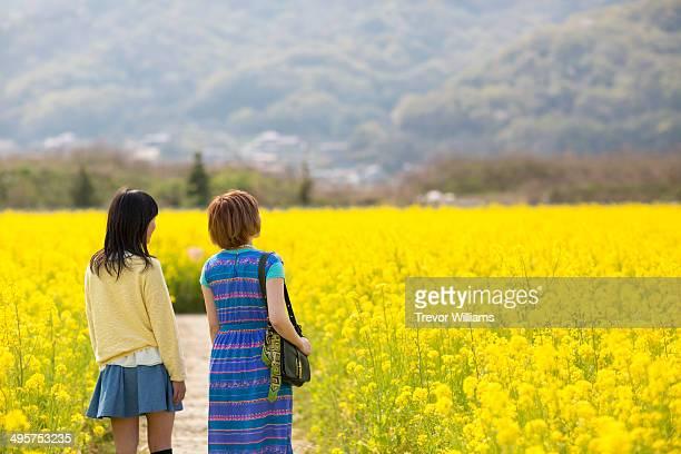 2 females in a field of flowers.