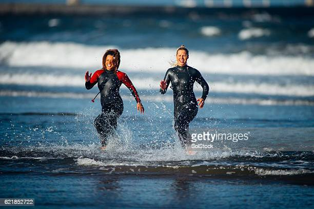Females in Wetsuits Running out of the Sea