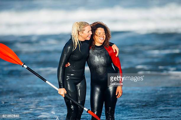 Females in Wetsuits Standing in the Sea