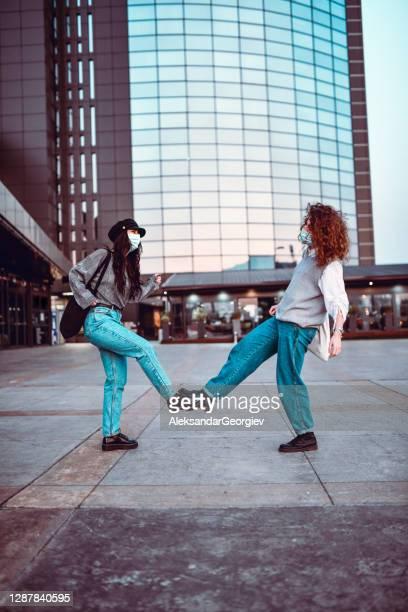 femelles faisant le salut de bosse de pied pour maintenir la distanciation sociale pendant covid-19 - éviter de se serrer la main photos et images de collection