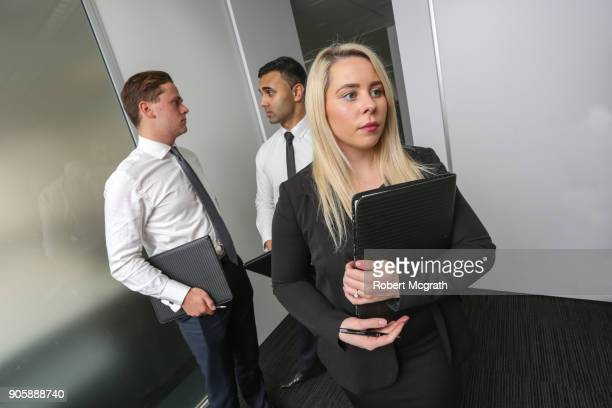 Females team leader get ready to enter meeting accompanied by two two male team members.