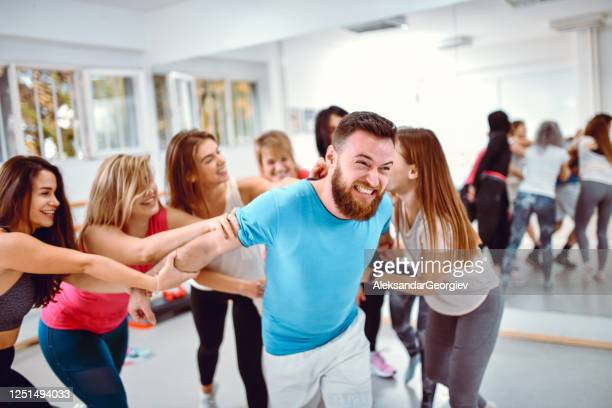females tormenting male in gym - female torture stock pictures, royalty-free photos & images