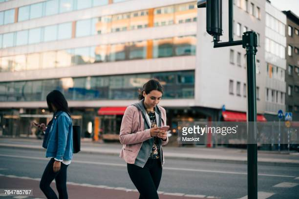 females walking on sidewalk while using smart phone against building in city - pedestrian crossing stock photos and pictures