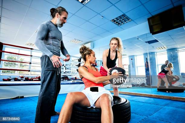 Females with personal trainer doing exercise at gym