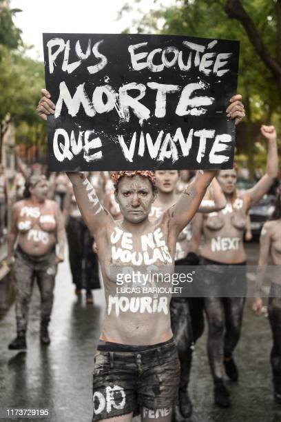 A Femen activist holds a placard reading More heard dead than alive and I didn't want to die during a protest action dedicated to the memory of the...
