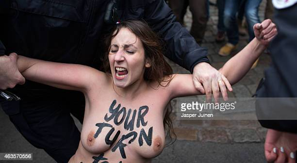 A Femen activist is detained by a policeman after jumping in front of the car with former IMF chief Dominique StraussKahn upon his arrival for his...