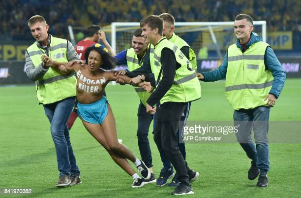 A 'femen' activist with the words 'Erdogan killer' written on her chest is escorted from the pitch by security personnel as she protests prior to the...