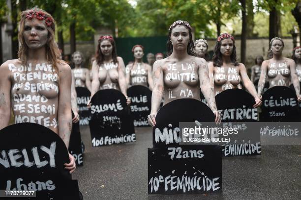 Femen activists hold placards shaped as tombstones reading the name and the age of each women killed this year by their partner during a protest...