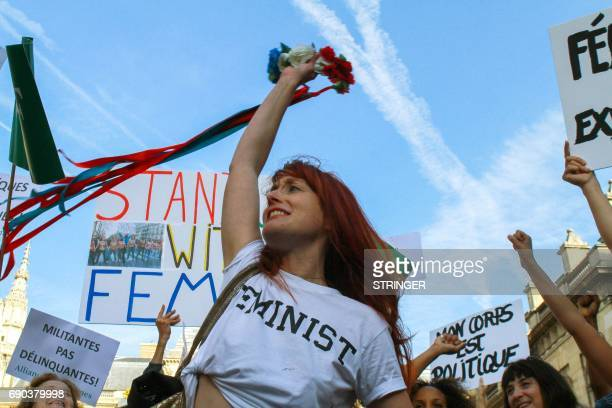 Femen activists holds signs at the courthouse where Femen activists go on trial for showing their breasts during a protest at a rally against gay...
