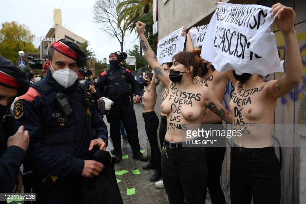"Femen activists with their bare chests reading ""Fascists out of ballot boxes"" are surrounded by Catalan regional police forces Mossos d'Esquadra as..."
