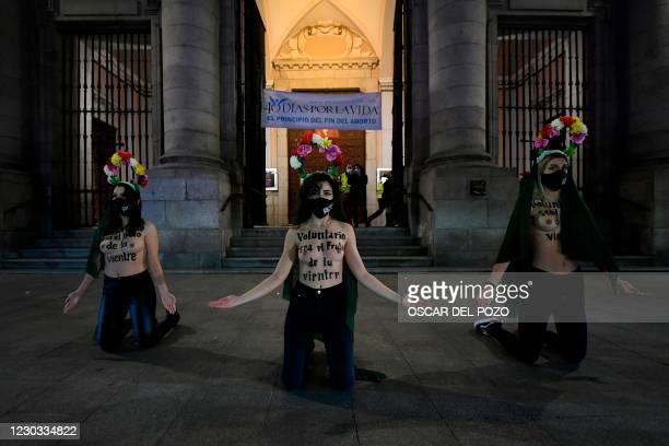 "Femen activists with their bare chests reading in Spanish ""May the fruit of your womb be voluntary"" kneel as they protest outside a church holding a..."