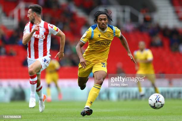 Femi Azeez of Reading FC is challenged by Stephen Ward of Stoke City during the Sky Bet Championship match between Stoke City and Reading at Bet365...