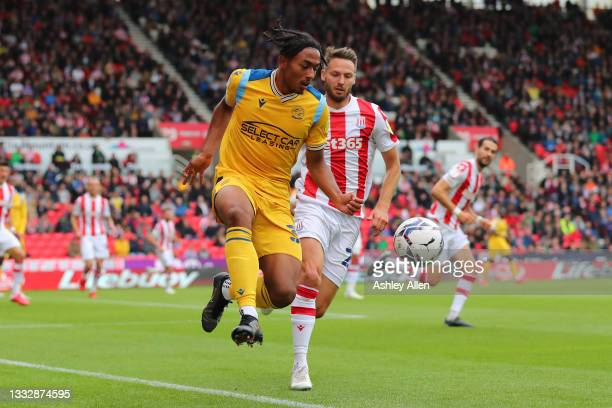 Femi Azeez of Reading FC is challenged by Tom Edwards of Stoke City during the Sky Bet Championship match between Stoke City and Reading at Bet365...