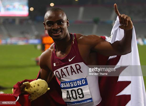 Femi Seun Ogunode of Qatar poses for photographs after breaking the Asian record and claiming the gold medal in the Men's 100m Final during day nine...
