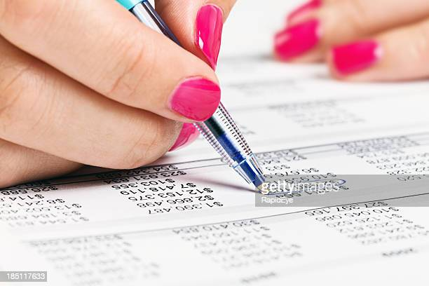 Feminine hand circles a number on financial document