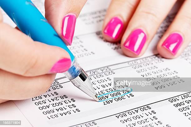 Mano femenina círculos figura en la hoja de cálculo financiera