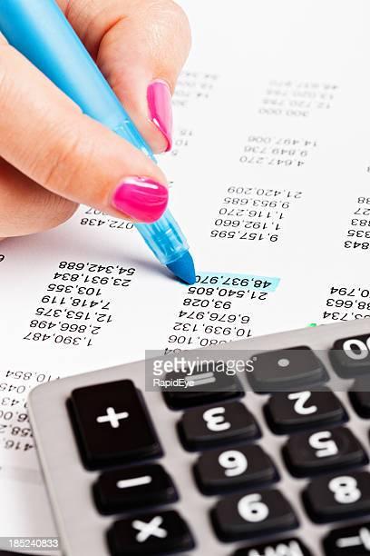 Main féminine les chiffres sur une feuille de calcul dans la zone bleue