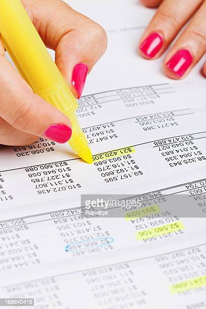 Feminine hands highlight figures on financial document in yellow