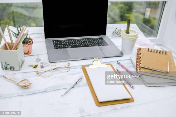 feminine workspace with laptop - feminidad fotografías e imágenes de stock